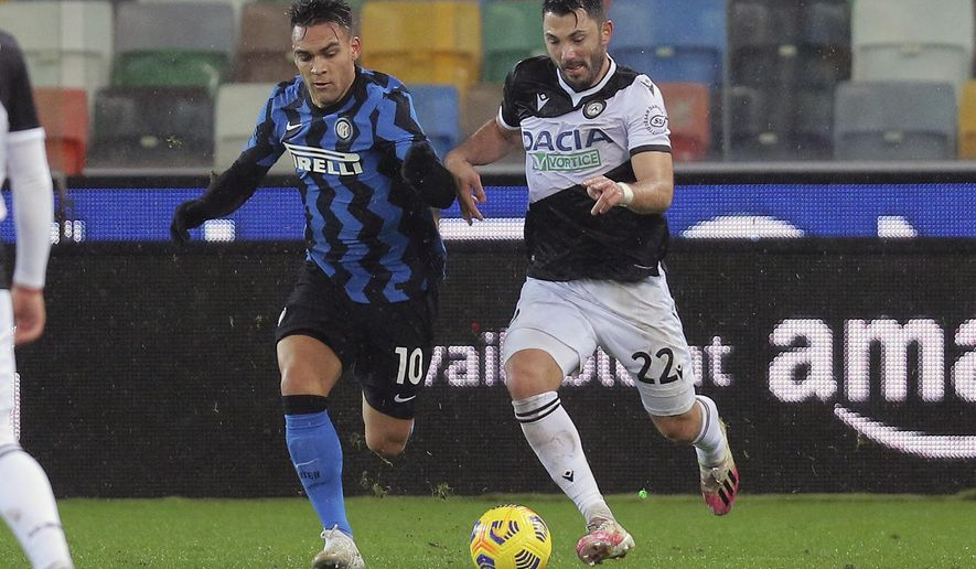 Inter's Lautaro Martinez, left, and Udinese's Tolgay Arslan go for the ball during the Serie A soccer match between Udinese and Inter Milan, at the Dacia Arena in Udine, Italy, Saturday, Jan. 23, 2021. (Gianpaolo Scognamiglio/LaPresse via AP)