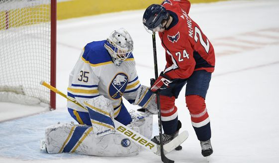 Washington Capitals' Connor McMichael (24) battles for the puck with Buffalo Sabres goaltender Linus Ullmark (35) during the first period of an NHL hockey game, Sunday, Jan. 24, 2021, in Washington. (AP Photo/Nick Wass)