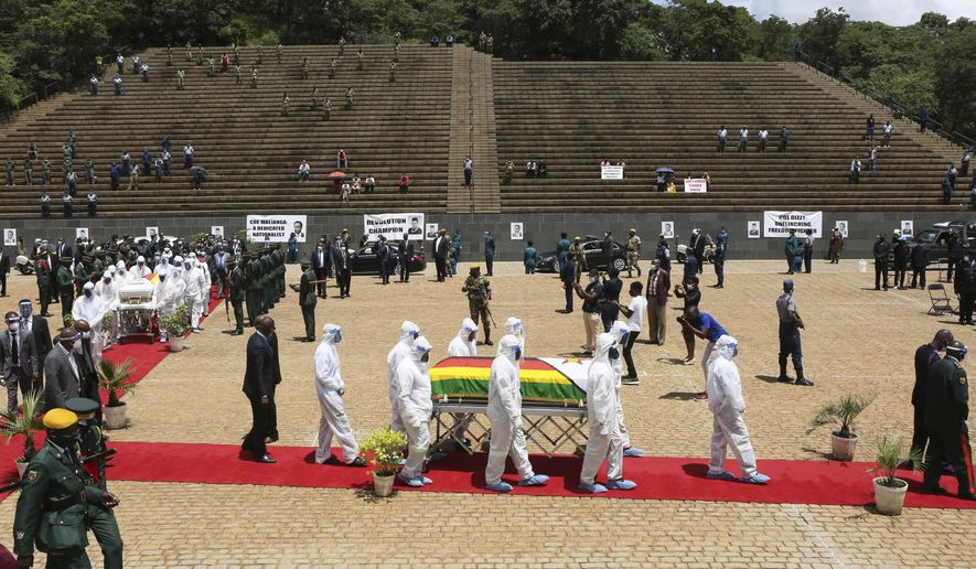 "Pallbearers carry the coffin of a government minister of Dr Ellen Gwaradzimba who died of COVID-19, at the Heroes Acre in Harare, Thursday, Jan. 21, 2021. Zimbabwean President Emmerson Mnangagwa who presided over the burial called the pandemic ""evil"" and urged people to wear masks, practice social distancing and sanitize, as cases across the country increased amid a fragile health system. (AP Photo/Tsvangirayi Mukwazhi)"