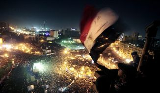 FILE - In this Jan. 25, 2012 file photo, people wave flags in Tahrir Square to mark the first anniversary of the popular uprising that led to the quick ouster of autocrat President Hosni Mubarak, in Cairo, Egypt. A decade later, thousands are estimated to have fled abroad to escape a state, headed by President Abdel Fattah el-Sissi, that is even more oppressive. (AP Photo/Amr Nabil, File)