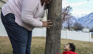 Lorimay Fuimaono-Ki, left, plays with one of her twins, Lima, right, outside of a relative's home in Provo, Utah, on Jan. 8, 2021. The young mother cannot stop the tears as she tries to explain what life has been like since her home, the U.S. territory of American Samoa, closed its borders to keep COVID-19 from ravaging the tiny string of Pacific Islands and atolls. (Annie Barker/The Deseret News via AP)