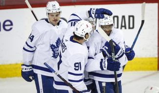 Toronto Maple Leafs' Wayne Simmonds, right, celebrates his goal against the Calgary Flames with teammates Auston Matthews, left, and John Tavares during second-period NHL hockey game action in Calgary, Alberta, Sunday, Jan. 24, 2021. (Jeff McIntosh/The Canadian Press via AP)