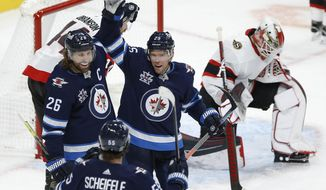 Winnipeg Jets' Mark Scheifele (55), Blake Wheeler (26) and Paul Stastny (25) celebrate Stastny's goal against Ottawa Senators goaltender Marcus Hogberg during the third period of an NHL hockey game Saturday, Jan. 23, 2021, in Winnipeg, Manitoba. (John Woods/The Canadian Press via AP)