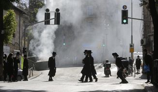 Men walk amid smoke from a dumpster fire, in an ultra-Orthodox neighborhood in Jerusalem, Sunday, Jan. 24, 2021. Ultra-Orthodox demonstrators clashed with Israeli police officers dispatched to close schools in Jerusalem and Ashdod that had opened in violation of health regulations on Sunday. (AP Photo/Sebastian Scheiner)