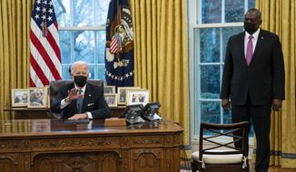 Secretary of Defense Lloyd Austin listens as President Joe Biden speaks before signing an Executive Order reversing the Trump era ban on transgender individuals serving in military, in the Oval Office of the White House, Monday, Jan. 25, 2021, in Washington. (AP Photo/Evan Vucci)