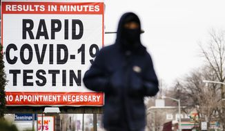 A person wearing face mask as a precaution against the coronavirus walks near a sign advertising a rapid COVID-19 testing site in Philadelphia, Monday, Jan. 25, 2021. (AP Photo/Matt Rourke)