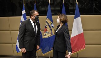 French Defense Minister Florence Parly, right, and his Greek counterpart Nikos Panagiotopoulos speak during their meeting in Athens, Monday, Jan. 25, 2021. Greece is due to sign a 2.3 billion euro ($2.8 billion) deal with France Monday to purchase 18 Rafale fighter jets to address tension with neighbor Turkey. (Louisa Gouliamaki/Pool via AP)