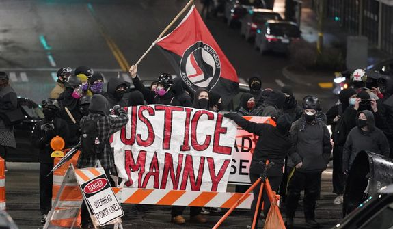 "A protester carries a flag that reads ""Antifascist Action"" near a banner that reads ""Justice for Manny,"" during a protest against police brutality, late Sunday, Jan. 24, 2021, in downtown Tacoma, Wash., south of Seattle. The protest came a day after at least two people were injured when a Tacoma Police officer responding to a report of a street race drove his car through a crowd of pedestrians that had gathered around him. Several people were knocked to the ground and at least one person was run over. The banner is in support of Manuel Ellis, a Black man who died in Tacoma after his airways were restricted by law enforcement officers in March 2020. (AP Photo/Ted S. Warren) **FILE**"