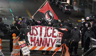 """A protester carries a flag that reads """"Antifascist Action"""" near a banner that reads """"Justice for Manny,"""" during a protest against police brutality, late Sunday, Jan. 24, 2021, in downtown Tacoma, Wash., south of Seattle. The protest came a day after at least two people were injured when a Tacoma Police officer responding to a report of a street race drove his car through a crowd of pedestrians that had gathered around him. Several people were knocked to the ground and at least one person was run over. The banner is in support of Manuel Ellis, a Black man who died in Tacoma after his airways were restricted by law enforcement officers in March 2020. (AP Photo/Ted S. Warren)"""