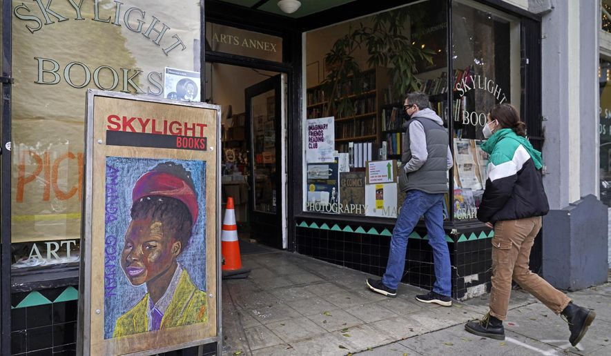 Eric and Tess from Pasadena, Calif., enter the Skylight Book store, decorated with a poster of American poet Amanda Gorman, in Los Feliz neighborhood of Los Angeles Monday, Jan. 25, 2021. California has lifted regional stay-at-home orders statewide in response to improving coronavirus conditions. Public health officials said Monday that the state will return to a system of county-by-county restrictions intended to stem the spread of the virus. Local officials could choose to continue stricter rules. The state is also lifting a 10 p.m. to 5 a.m. curfew. (AP Photo/Damian Dovarganes)