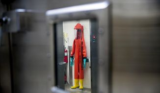 In this March 19, 2020, file photo, a biosafety protective suit for handling viral diseases are hung up in a biosafety level 4 training facility at U.S. Army Medical Research and Development Command at Fort Detrick in Frederick, Md., where scientists are working to help develop solutions to prevent, detect and treat the coronavirus. China is trying to spread doubt about the effectiveness of Western vaccines and the origin of the coronavirus as a World Health Organization-selected team of scientists are in the city where the pandemic first broke out. (AP Photo/Andrew Harnik, File)