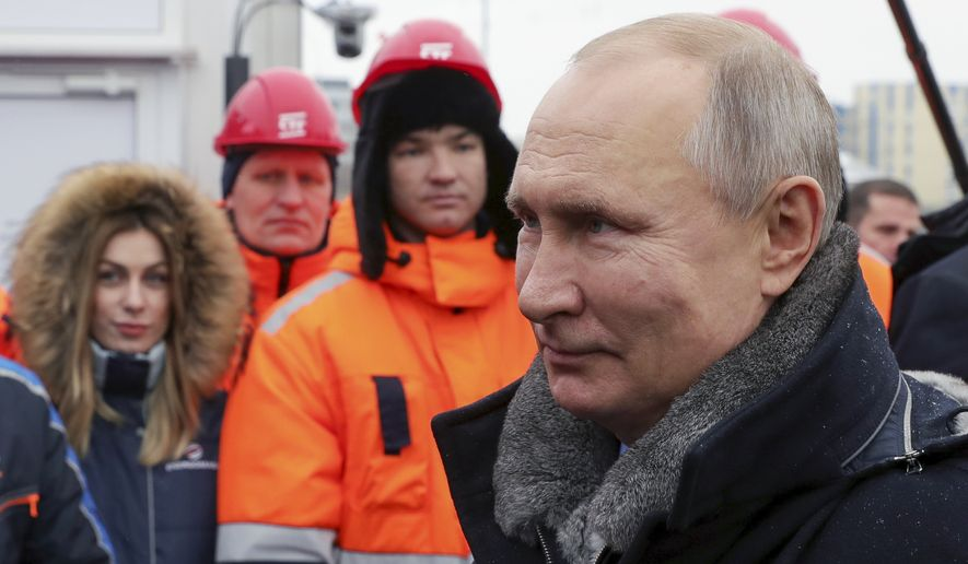 """Russian President Vladimir Putin speaks to workers as he attends an opening ceremony of the road junction of the M-10 """"Russia"""" highway, connecting Moscow and St. Petersburg, in Khimki outside Moscow, Russia, Tuesday, Jan. 26, 2021. (Mikhail Klimentyev, Sputnik, Kremlin Pool Photo via AP)"""
