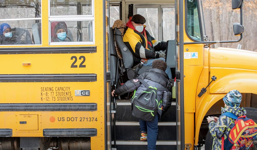 Rycc Smith welcomes Montello Elementary School students as they board his bus outside the Lewiston, Maine school Thursday afternoon, Jan. 21, 2021 after the first day back in nearly a month. The entire school district switched to all remote learning after an uptick in COVID-19 cases last month. Smith has been driving a school bus for the past 40 years and said the students have been very cooperative following the protocols. (Russ Dillingham/Sun Journal via AP)