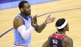 Houston Rockets' John Wall applauds a call, next to Washington Wizards' Bradley Beal during the fourth quarter of an NBA basketball game Tuesday, Jan. 26, 2021, in Houston. (Carmen Mandato/Pool Photo via AP)
