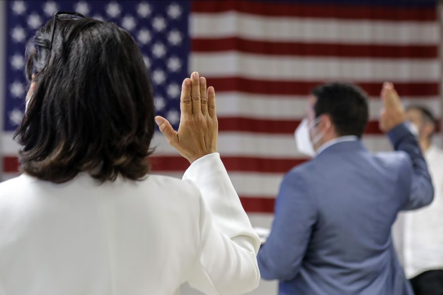 In this July 2, 2020, file photo, people take the oath of citizenship during a naturalization ceremony at U.S. Citizenship and Immigration Service's Field Office in New York. (AP Photo/Frank Franklin II, File)