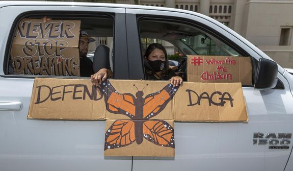 In this June 18, 2020, file photo, people hold signs during a vehicle caravan rally to support the Deferred Action for Childhood Arrivals program (DACA), around MacArthur Park in Los Angeles. (AP Photo/Damian Dovarganes, File)