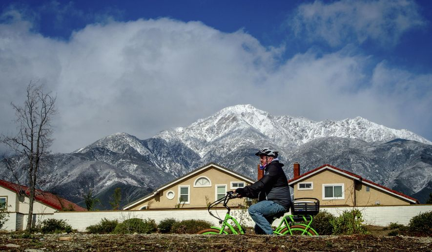 A cyclist rides a bike along the Pacific Electric Trail in Rancho Cucamonga, Calif. against a backdrop of the snow-capped San Gabriel Mountains on Monday, Jan. 25, 2021. (Watchara Phomicinda/The Orange County Register via AP)