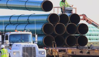 FILE - In this May 9, 2015, file photo, workers unload pipes in Worthing, S.D., for the Dakota Access oil pipeline that stretches from the Bakken oil fields in North Dakota to Illinois. A federal appeals court on Tuesday, Jan. 26, 2021, upheld the ruling of a district judge who ordered a full environmental impact review of the Dakota Access pipeline in North Dakota. Following a complaint by the Standing Rock Sioux Tribe, U.S. District Judge James Boasberg said in April 2020 that a more extensive review was necessary than the one already conducted by the U.S. Army Corps of Engineers.  (AP Photo/Nati Harnik, File)