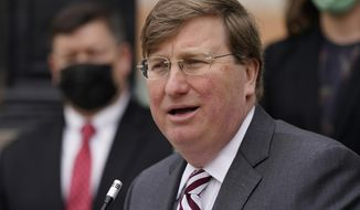 Gov. Tate Reeves speaks about his hopes for the state's continued economic growth during the coronavirus pandemic after announcing the permanent appointment of John Rounsaville, background left, as director of the Mississippi Development Authority, during a news conference, Tuesday, Jan. 19, 2021, in Jackson, Miss. Rounsaville had been serving as interim director since 2020. (AP Photo/Rogelio V. Solis)