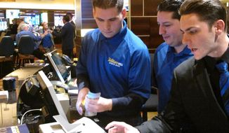 This Oct. 25, 2018 photo, employees at the sports book at the Tropicana casino in Atlantic City N.J. count money moments before it opened. Gambling companies in the U.S. are increasingly bringing different forms of gambling together, including sports betting, casino gambling, internet gambling and daily fantasy sports, and partnering with media companies as they seek to increase revenue. (AP Photo/Wayne Parry)
