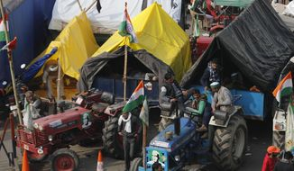 Indian farmers sit on their tractor after arriving at the Delhi-Uttar Pradesh border for Tuesday's tractor rally in New Delhi, India, Monday, Jan. 25, 2021. (AP Photo/Manish Swarup)