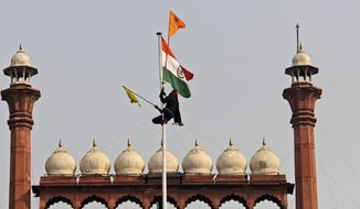 A Sikh man hangs on to a pole holding a Sikh religious flag along with a farm union flag at the historic Red Fort monument in New Delhi, India, Tuesday, Jan. 26, 2021. Tens of thousands of protesting farmers drove long lines of tractors into India's capital on Tuesday, breaking through police barricades, defying tear gas and storming the historic Red Fort as the nation celebrated Republic Day. (AP Photo/Supreet Sapkal)