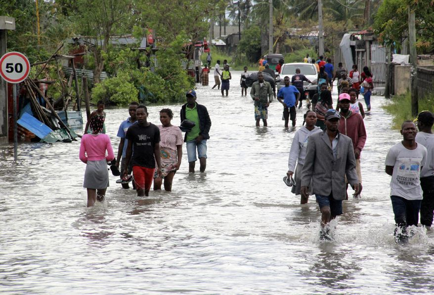 People make their way through floodwaters in Beira Mozambique, Saturday, Jan. 23, 2021. The Mozambican port city of Beira breathed a sigh of relief as Cyclone Eloise caused less damage than feared as it passed through, but the danger of flooding remained in a region still recovering from a devastating cyclone two years ago. (AP Photo)