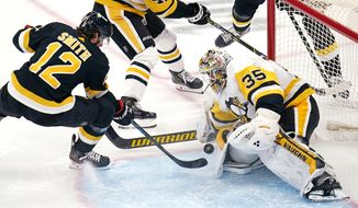 Pittsburgh Penguins goaltender Tristan Jarry (35) makes a save on a shot by Boston Bruins' Craig Smith (12) during the first period of an NHL hockey game, Tuesday, Jan. 26, 2021, in Boston. (AP Photo/Charles Krupa)