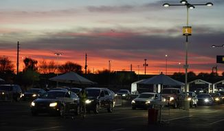 FILE - In this Jan. 12, 2021, file photo, vehicles line up so people can get their COVID-19 vaccination cards after being vaccinated in a pre-registered drive-thru in the parking lot of the State Farm Stadium in Glendale, Ariz. Arizona reported 4,748 additional known COVID-19 cases and 209 deaths on Tuesday, Jan. 26 the one-year anniversary of the announcement of the state's first confirmed coronavirus case in the outbreak that has since claimed thousands of lives statewide. (AP Photo/Ross D. Franklin, File)
