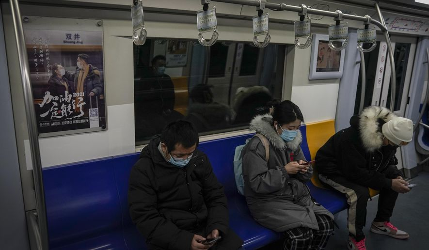 """Commuters wearing face masks to help curb the spread of the coronavirus ride on a subway train near an advertisement carrying the words """"Come on 2021, It will work"""" in Beijing, Tuesday, Jan. 26, 2021. Countries must cooperate more closely in fighting the challenges of the pandemic and climate change and in supporting a sustainable global economic recovery, Chinese President Xi Jinping said on Monday in an address to the World Economic Forum. (AP Photo/Andy Wong)"""