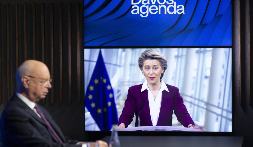 German Klaus Schwab, left, founder and executive chairman of the World Economic Forum, WEF, listens to European Commission President Ursula von der Leyen, displayed on a video screen, during a conference at the Davos Agenda in Cologny near Geneva, Switzerland, Tuesday, Jan. 26, 2021. The Davos Agenda from Jan. 25 to Jan. 29, 2021, is an online edition due to the coronavirus disease (COVID-19) outbreak. (Salvatore Di Nolfi/Keystone via AP)