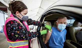 Registered Nurse Lisa Strickland, left, administers a COVID-19 vaccine to Tracy Atkinson during the drive-up inoculation event at Craig Houghton Elementary School in Augusta, Ga., Tuesday, Jan. 19, 2021. (Michael Holahan/The Augusta Chronicle via AP)