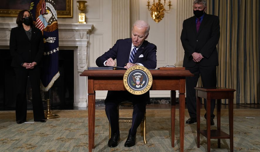 President Joe Biden signs an executive order on climate change, in the State Dining Room of the White House, Wednesday, Jan. 27, 2021, in Washington. Vice President Kamala Harris looks on at left. (AP Photo/Evan Vucci)
