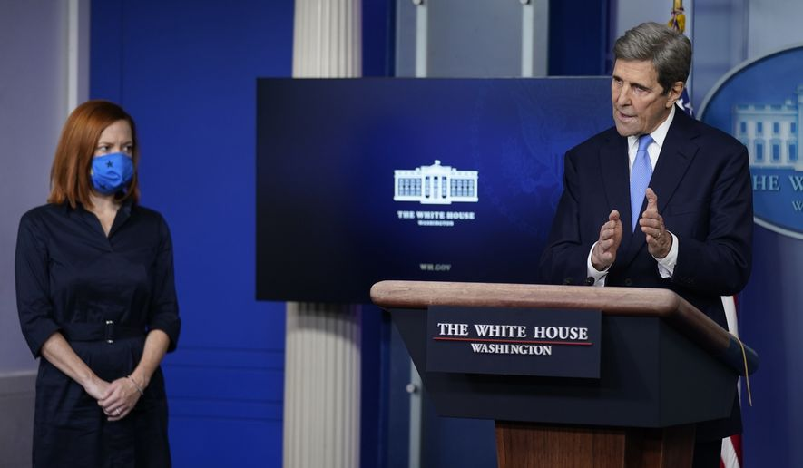 Press secretary Jen Psaki listens as Special Presidential Envoy for Climate John Kerry speaks during a press briefing at the White House, Wednesday, Jan. 27, 2021, in Washington. (AP Photo/Evan Vucci)