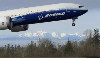 In this Jan. 25, 2020, photo a Boeing 777X airplane takes off on its first flight with the Olympic Mountains in the background at Paine Field in Everett, Wash. Boeing is reporting another huge loss, this one because of a setback to its 777X widebody jetliner. Boeing said Wednesday, Jan. 27, 2021, it lost $8.4 billion in the fourth quarter on weaker demand for planes during the pandemic. (AP Photo/Ted S. Warren)