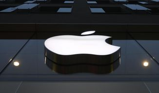 The logo of Apple is illuminated at a store in the city center in Munich, Germany, Wednesday, Dec. 16, 2020. Apple's delayed launch of its latest iPhones unleashed a holiday buying frenzy that propelled sales of the trendsetting company's most popular product to its fastest start in years. The apparently pent-up demand for four different iPhone 12 models highlighted Apple's latest quarterly report Wednesday, Jan. 27, 2021. (AP Photo/Matthias Schrader)