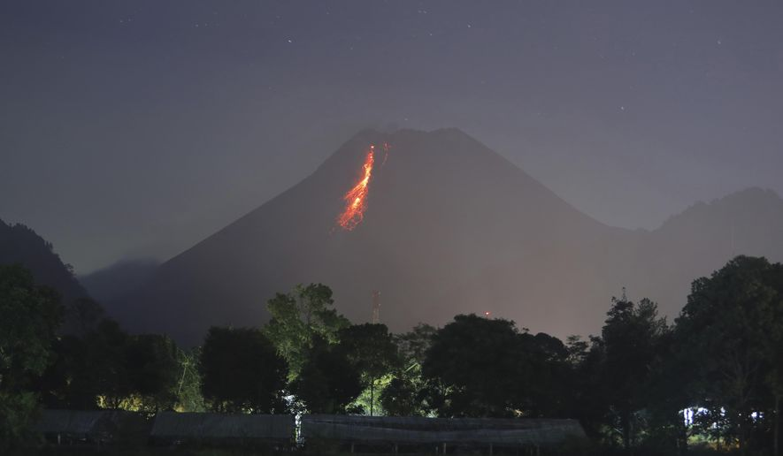 In this time-lapsed photo, hot lava runs down from Mount Merapi as its activity continues since local geological authority raised the alert level to the second-highest level in November, in Kaliurang, Indonesia, early Sunday, Jan. 24, 2021. Merapi is one of the most volatile among the country's more than 120 volcanoes. (AP Photo/Trisnadi)