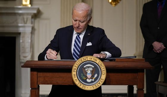 President Joe Biden signs an executive order on climate change, in the State Dining Room of the White House, Wednesday, Jan. 27, 2021, in Washington. (AP Photo/Evan Vucci)