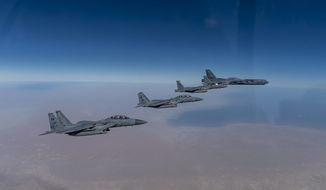 """In this Wednesday, Jan. 27, 2021 handout photo, released by the U.S. Air Force, a B-52 bomber from the 2nd Bomb Wing of Barksdale Air Force Base in Louisiana, right, flies with Royal Saudi Air Force F-15s during a mission in the Middle East. The U.S. military said Wednesday it again flew a B-52 bomber over the Middle East """"to deter potential aggression"""" amid tensions with Iran. (U.S. Air Force/Senior Airman Roslyn Ward, via AP)"""