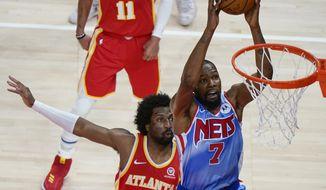 Brooklyn Nets forward Kevin Durant (7) shoots next to Atlanta Hawks' Solomon Hill during the first half of an NBA basketball game Wednesday, Jan. 27, 2021, in Atlanta. (AP Photo/Brynn Anderson)