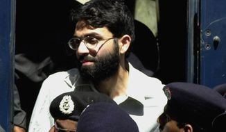 """FILE - In this March 29, 2002 file photo, Ahmed Omar Saeed Sheikh, a British-Pakistani man accused in the 2002 killing of the American Wall Street Journal reporter Daniel Pearl appears at the court in Karachi, Pakistan. In a dramatic turn of events, Sheikh, a man convicted and later acquitted in the 2002 murder of Pearl admitted a """"minor"""" role in his death, upending 18 years of denials, the Pearl family lawyer said Wednesday, Jan. 27, 2021. (AP Photo/Zia Mazhar, File)"""