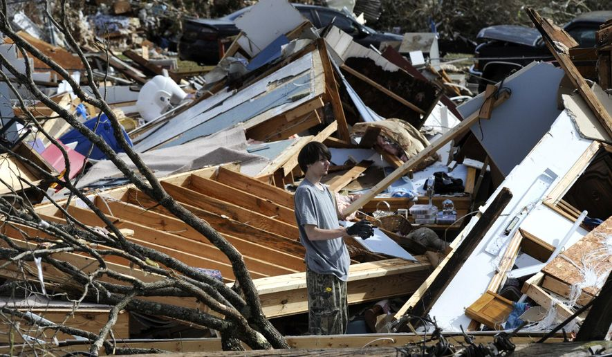 James Scott, 19, pauses while picking through the remains of his home, which was destroyed by a tornado, on Tuesday, Jan. 26, 2021, in Fultondale, Ala. Scott, who survived with his mother and sister, had never lived anywhere else and isn't sure where he will wind up after the storm. (AP Photo/Jay Reeves)