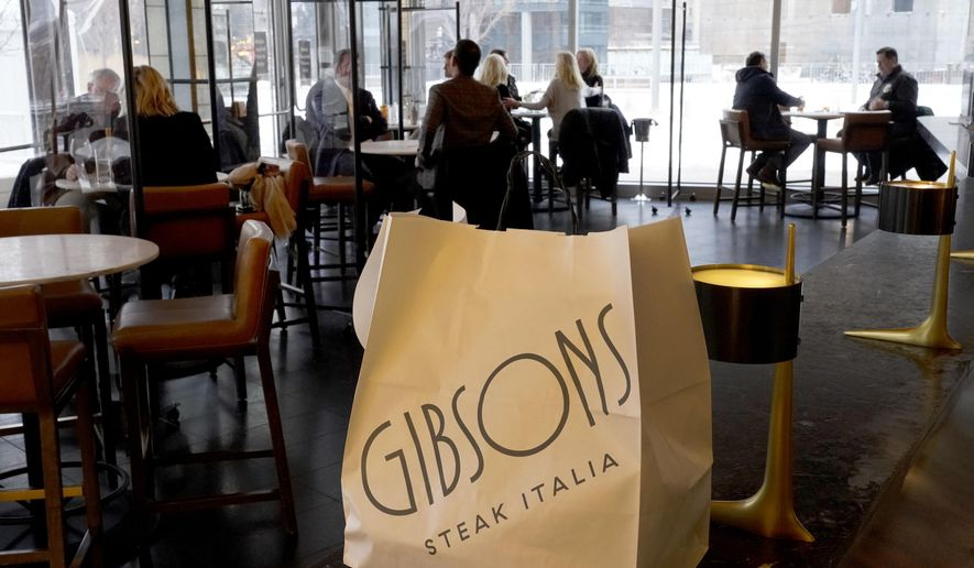 A takeout bag sits at the bar Wednesday, Jan. 27, 2021, as patrons return to indoor dining at Gibsons Italia restaurant in Chicago. Several states are loosening their coronavirus restrictions on restaurants and other businesses because of improved infection and hospitalization numbers but are moving cautiously. (AP Photo/Charles Rex Arbogast) **FILE**