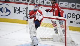 Washington Capitals goaltender Vitek Vanecek, front, celebrates after the team's NHL hockey game against the New York Islanders, Thursday, Jan. 28, 2021, in Washington. At right is defenseman Jonas Siegenthaler (34). (AP Photo/Nick Wass)