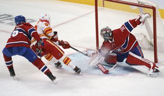Montreal Canadiens goaltender Carey Price stops Calgary Flames' Nikita Nesterov during third-period NHL hockey game action in Montreal, Thursday, Jan. 28, 2021. (Paul Chiasson/The Canadian Press via AP)