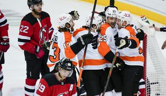 Philadelphia Flyers' Nate Prosser, right, celebrates with teammates after scoring a goal during the first period of an NHL hockey game against the New Jersey Devils on Thursday, Jan. 28, 2021, in Newark, N.J. (AP Photo/Frank Franklin II)