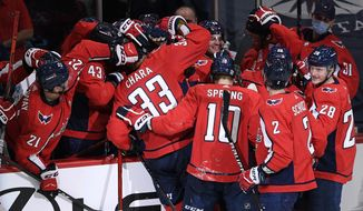 Washington Capitals defenseman Zdeno Chara (33) is mobbed by teammates after he scored a goal during the second period of an NHL hockey game against the New York Islanders, Thursday, Jan. 28, 2021, in Washington. (AP Photo/Nick Wass)