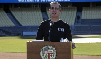 FILE - In this Jan. 15, 2021, file photo, Los Angeles Mayor Eric Garcetti addresses a press conference held at the launch of a mass COVID-19 vaccination site at Dodger Stadium in Los Angeles. Garcetti made clear in December that he would wait his turn to receive a COVID-19 vaccination, echoing county policy that nursing home residents, people 65 and older and medical workers will be first in line. But the 49-year-old Democrat was quietly vaccinated last week at the recommendation of medical personnel, after spending several days assisting healthcare workers at a large coronavirus vaccination center at Dodger Stadium. (Irfan Khan/Los Angeles Times via AP, Pool)