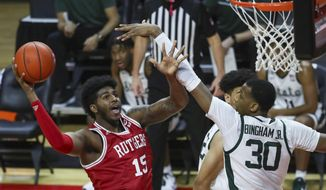 Rutgers center Myles Johnson (15) shoots as he is defended by Michigan State forward Marcus Bingham Jr. (30) during the first half of an NCAA college basketball game against Rutgers, Thursday, Jan. 28, 2021, in Piscataway, N.J. (Andrew Mills/NJ Advance Media via AP)