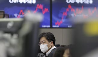 A currency trader watches computer monitors at the foreign exchange dealing room in Seoul, South Korea, Friday, Jan. 29, 2021. Asian stock markets were mixed Friday after Wall Street rebounded from its biggest loss in nearly three months, while Japan reported December factory output weakened. (AP Photo/Lee Jin-man)
